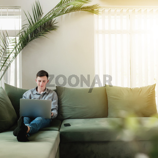 Young guy sitting at green sofa with gray laptop and black phone
