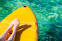 yellow stand up paddle board with visible legs of a young girl on the turquoise surface of the ocean