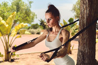 Young woman using expander working out outdoor