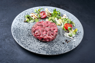 Modern style gourmet tartar raw from beef filet with lettuce