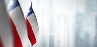 Small flags of Chile on a blurry background of the city