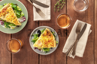 Slices of a French quiche with salmon, with green salad leaves, thyme and white wine