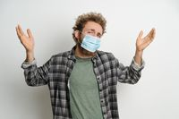 Young man in protective face mask with curly hair showing I don't know gesture with both hands isolated on white background. Portrait of confused sick young man on white background