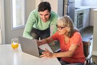 Mann hilft Senior Mutter beim Email schreiben am Laptop