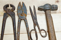 Hammer and nippers on wood background