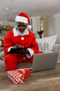 Senior african american man wearing a costume of santa claus and writing on clipboard