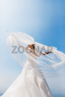 An elegant bride stands with her arms outstretched, the wind wind will blow a veil around her