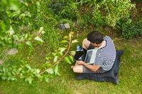 Mann am Laptop Computer im Garten im Sommer