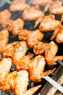 Delicious juicy chicken wings on outdoors grill