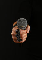 Man hand with microphone isolated on black
