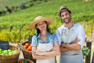 Portrait of happy couple with arms crossed at farm
