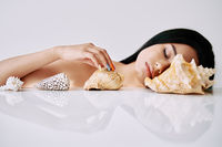 Fashion portrait of beautiful african american woman closed eyes with different seashells
