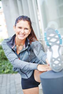 Lachende Frau dehnt sich vor dem Jogging