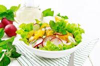 Salad of radish and orange with mint on board