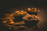 Organic cocoa beans in small bowls on brown background. Baking and cooking ingredients