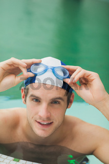 Smiling man taking off goggles