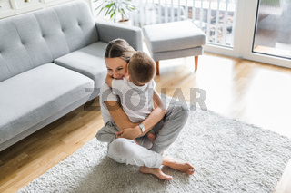 Mother with her son playing in their living room