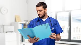 male doctor reading medical report in folder
