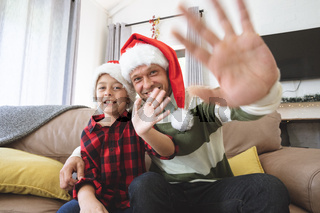 Portrait of man and son wearing Santa hat waving at home