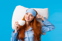 Perfect morning of princess. Cheerful, tender redhead woman with long ginger hair, wearing sleep mask and pyjama, stretching in bed feeling fresh and energized, drink morning coffee, blue background