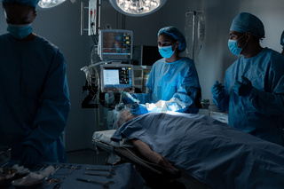 Diverse surgeons with face masks and protective clothing during operation, sedating patient