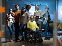 Disabled businesswoman in a wheelchair at the office with coworkers team