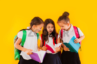 The little schoolgirls are reading the books at the yellow background