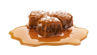 Salted toffee candies with caramel sauce isolated on white background