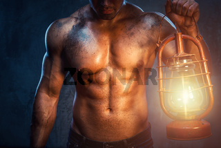 Muscular man holding oil lamp