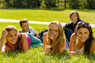 Students laying on grass in park campus