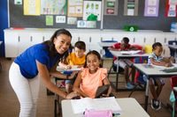 Portrait of african american female teacher and disabled girl smiling in class at elementary school