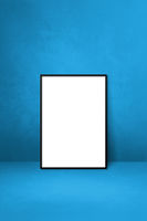 Black picture frame leaning on a blue wall