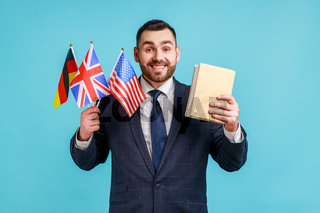 Satisfied businessman or teacher wearing official style suit, holding flags of Germany, Great Britain and USA and book, looking at camera with smile.