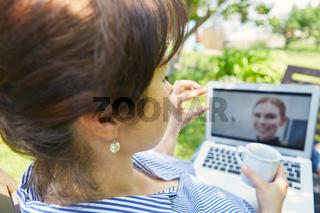 Freiberufler am Laptop PC beim Videochat im Garten