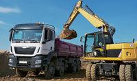 Excavator loads trucks with excavation