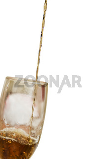Alcohol drink pours into the glass isolated over white