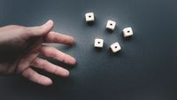 Throwing the dice on a dark grey background.