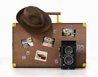 Vintage camera and hat standing on suitcase with old photos. Images on the photos are from my own portfolio. 3D illustration