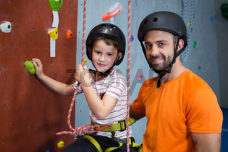 Trainer assisting boy in rock climbing at fitness studio