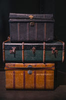 Pile of vintage, warn travel suitcases or trunks on the floor