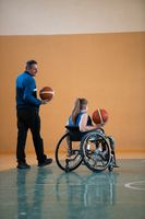 a sports basketball coach explains to a disabled woman in a wheelchair which position to play during a game