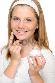 Cheerful young girl applying moistuizer face cream