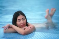Brunette lies in thermal water in pool at spa and relaxes.