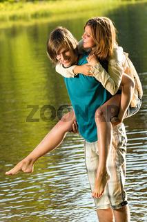 Girl piggyback riding his boyfriend in water