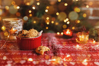 Red festive bowl full with Christmas cookies, blurred Christmas fir tree lights