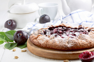 Open pie or galette with red plums and cardamom.