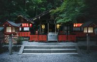 Nonomiya Shrine in the evening with lanterns surrounded by lush forest in Kyoto, Japan