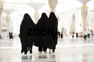 Three Moslim women walking outdoors