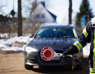 Feuerwehr Feuerwehrmann sperrt eine Strasse