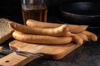 Smoked frankfurter sausages on cutting board.